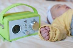 Baby sleeping with alarm clock Stock Photo
