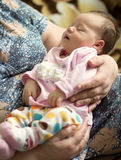 Baby sleeping in the arms of  grandmother Stock Photo