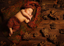 Baby Sleeping Autumn Background, New Born Kid Asleep, Newborn. Baby Sleeping on Autumn Background, New Born Kid Asleep in Leaves, Newborn Lying on Brown Wood royalty free stock photography