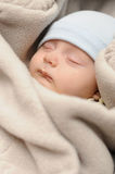 Baby in sleeping bag. Little baby peacefully resting in soft grey sleeping bag Stock Photo