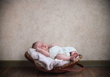 Baby sleeping in the basket on the wooden floor Stock Photo
