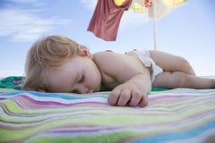 Baby sleeping on beach towel Stock Photography