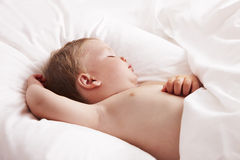 Baby sleeping in bed Stock Photos