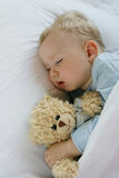 Baby sleeping in bed. 18 months old baby boy slepping in bed with sweet teddy bear. Little baby dreamer Stock Photography