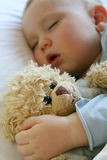 Baby sleeping in bed. 18 months old baby boy slepping in bed with sweet teddy bear. Little baby dreamer Royalty Free Stock Images