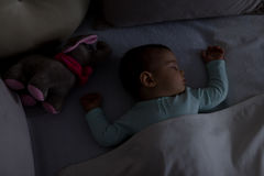 Baby Sleeping on the bed. Adorable baby sleeping at night. Little girl in pajama taking a nap in dark room with toy Stock Images
