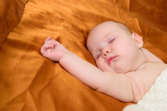 Baby sleeping on the bed and nestled towel Stock Photography