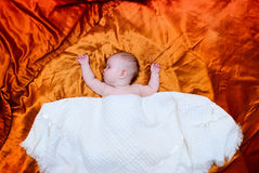 Baby sleeping on the bed and nestled towel Royalty Free Stock Photo