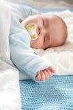Baby sleeping on blue blanket Stock Photos