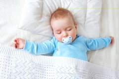 Baby sleeping on blue blanket. Seven month old baby sleeping on white blanket and pillow. Sleepy child on soft bedding with pacifier Stock Photos