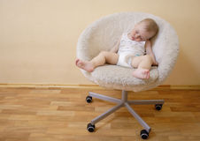 Baby sleeping on chair. Cute baby boy sleeping on cosy modern chair Royalty Free Stock Photography