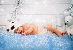 The baby is sleeping on Christmas. The baby in a hat is sleeping on a blue blanket on Christmas on the background of a lights Royalty Free Stock Photo