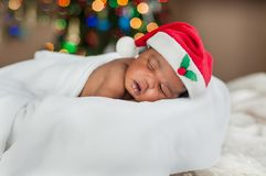 A baby sleeping comfy in blanket and Santa hat under colourful Christmas lights royalty free stock images