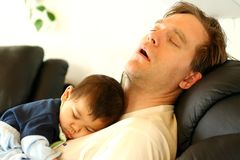Baby sleeping on dad's chest Stock Images