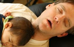 Baby sleeping on dad's chest stock image