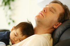 Baby sleeping on dad's chest royalty free stock photo