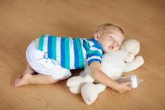 Baby sleeping on floor with toy and milk bottle. royalty free stock photo