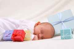 Baby Sleeping By Gift Boxes Royalty Free Stock Photos