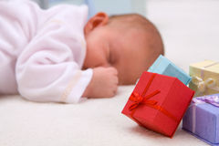 Baby Sleeping By Gift Boxes Royalty Free Stock Image