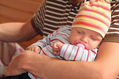 Baby sleeping on hands of man royalty free stock photos