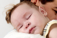Baby sleeping on her father arms Stock Images
