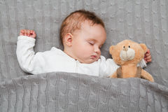Baby sleeping with her teddy bear Stock Photos