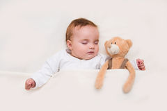 Baby sleeping with her teddy bear. Infant lying on the bed. Baby sleeping with her teddy bear, new family and love concept stock photography