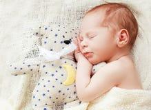 Baby sleeping with her teddy bear Stock Photos