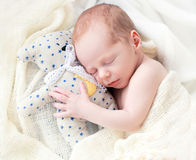Baby sleeping with her teddy bear Stock Images