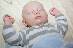 Baby Sleeping. A baby sleeping with his arms next to his head Royalty Free Stock Photography