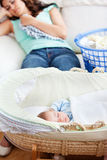 Baby sleeping in his cradle with mother on couch. Cute baby sleeping in his cradle with his mother lying on the couch in the background in the living-room Royalty Free Stock Image