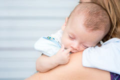 Baby sleeping on his mother`s shoulder Royalty Free Stock Photos