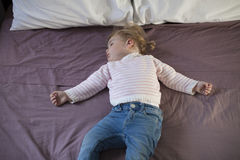 Baby sleeping on king bed. Blonde caucasian baby nineteen month age with blue jeans trousers pink and white stripped jersey sleeping on brown sheets king bed royalty free stock photography