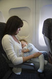 Baby Sleeping On Mother's Laps In Airplane. Baby girl sleeping on mother's laps while traveling in airplane Royalty Free Stock Photography