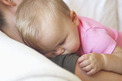 Baby Sleeping On Mother's Shoulder Royalty Free Stock Images