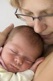 Baby sleeping in mothers arm stock image