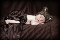 Baby with bear hat. Newborn baby sleeping while wearing brown bear hat stock photos