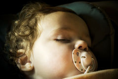 Baby sleeping with pacifier Stock Photography