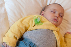 Baby sleeping with pacifier. Face of Baby with yellow onesie sleeping with pacifier Stock Images