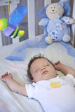Baby sleeping peacefully in her crib Stock Photography