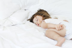Baby sleeping peacefully in a white bed Royalty Free Stock Images