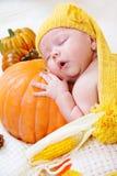 Baby sleeping on a pumpkin