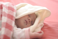 Baby sleeping in red Stock Photos