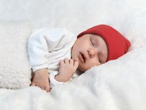 Baby sleeping in a red cap on white Stock Image