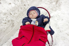 Baby sleeping in red sledge Royalty Free Stock Photo