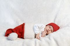 Baby sleeping in Santa hats Stock Image