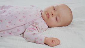 Baby Sleeping Sound on the Bed. A baby sleeping sound on a white bed at home. Medium dolly shot stock footage