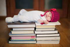 Baby sleeping on stack of books Stock Photo