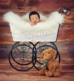 Baby sleeping. A studio vintage photo of a newborn baby sleeping inside a carriage Royalty Free Stock Photography