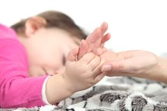 Baby sleeping takes the hand of her mother Royalty Free Stock Photos